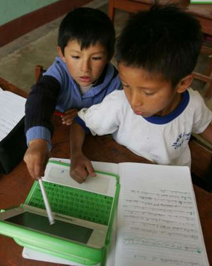 Erick, left, and Fernando use their XO laptop during a nature class in Arahuay, Peru, an Andean hilltop village. Photo: MARTIN MEJIA, ASSOCIATED PRESS