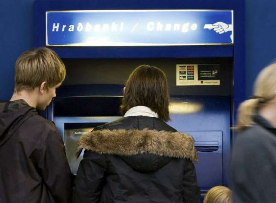 Customers make withdrawals at a branch of Landsbanki in Kopavogur. A national bankruptcy in Iceland as the economy implodes would send shock waves across Europe. Photo: ARNI TORFASON, ASSOCIATED PRESS