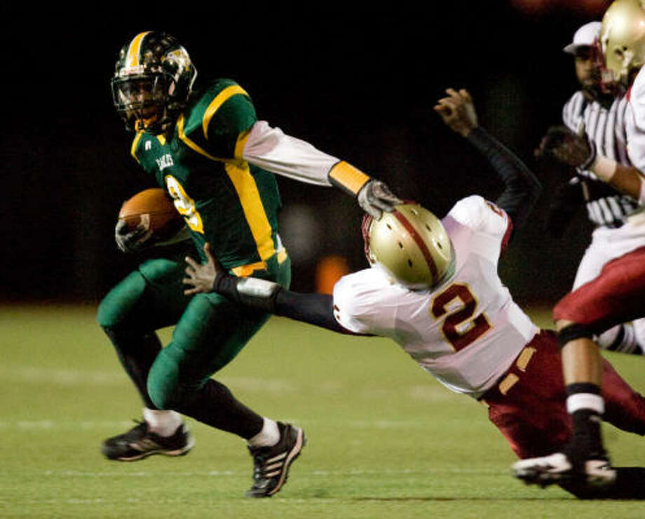 Klein Forest running back Dominic Wilkins (left) gives Cy Woods' Jarel  Richards a stiff arm during Friday's game. Photo: Bob Levey, For The Chronicle