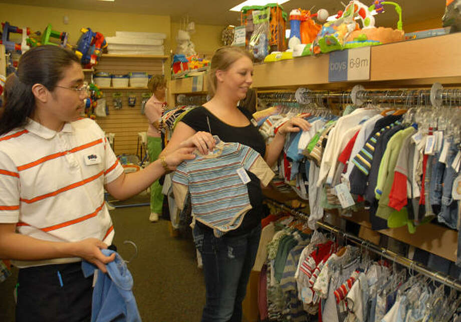 Store employees Parker Kemp and Jacelyn Miller hang up some gently used toddler clothes at the Kid to Kid resale shop, 6777 Woodlands Parkway. Customers at area resale shops have increased as customers try to save money. Photo: David Hopper, For The Chronicle