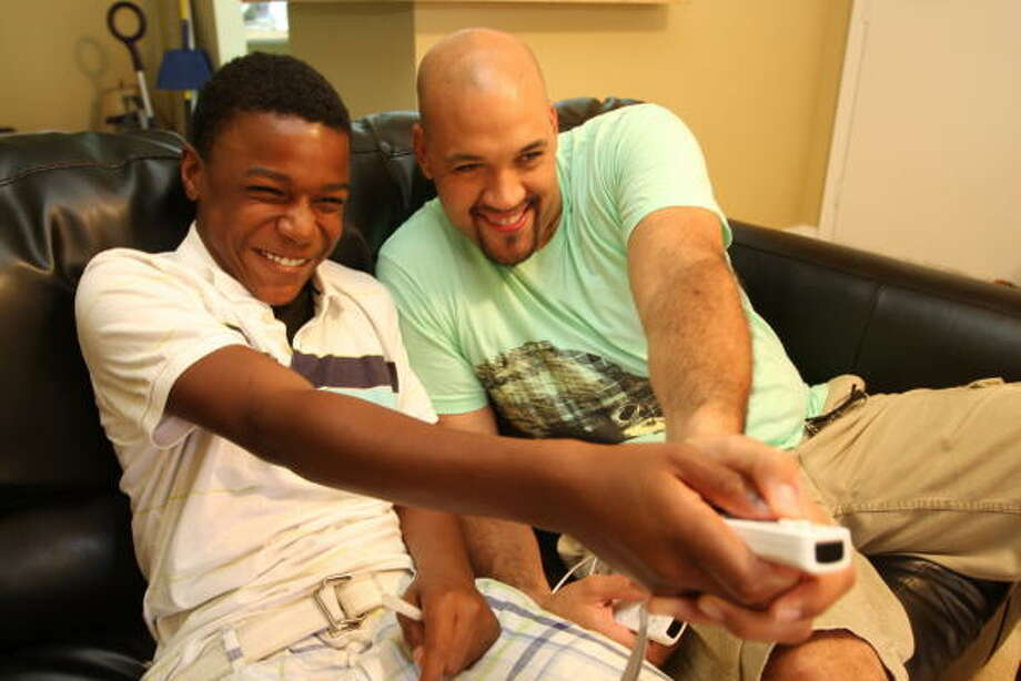 """Carlos Williams of Richmond enjoys playing video games with """"Chris,"""" whose adoption will become official in July. Photo: Suzanne Rehak, For The Chronicle"""