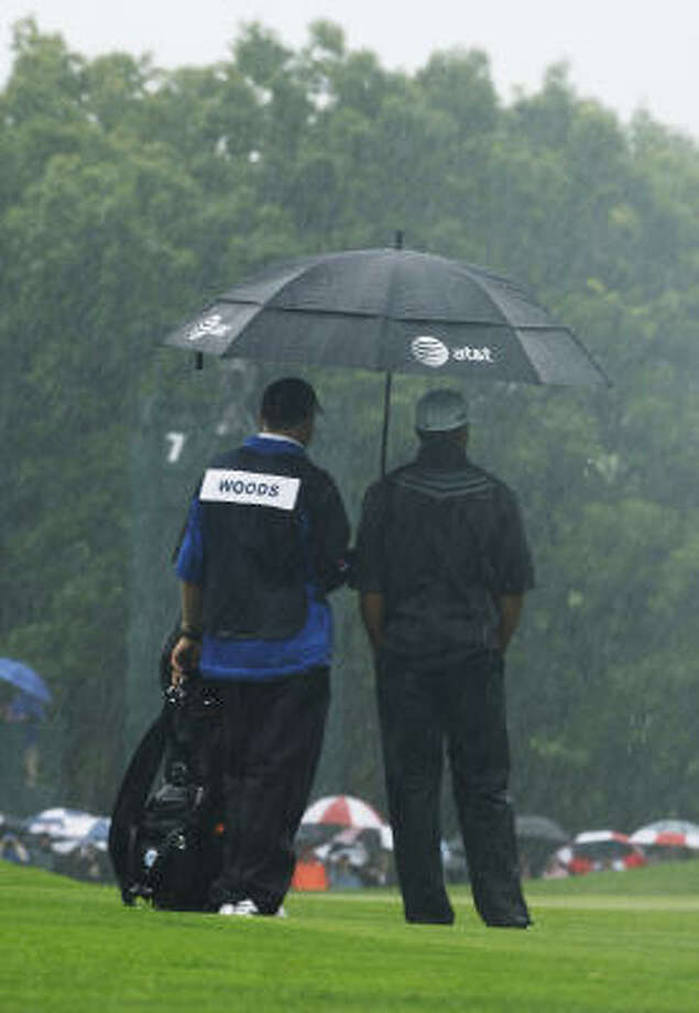 The rain picks up as Tiger Woods, with caddie Steve Williams, plays the sixth hole. It was Woods' last hole of the day, and he birdied it to end the day at 1-over. Photo: Morry Gash, AP
