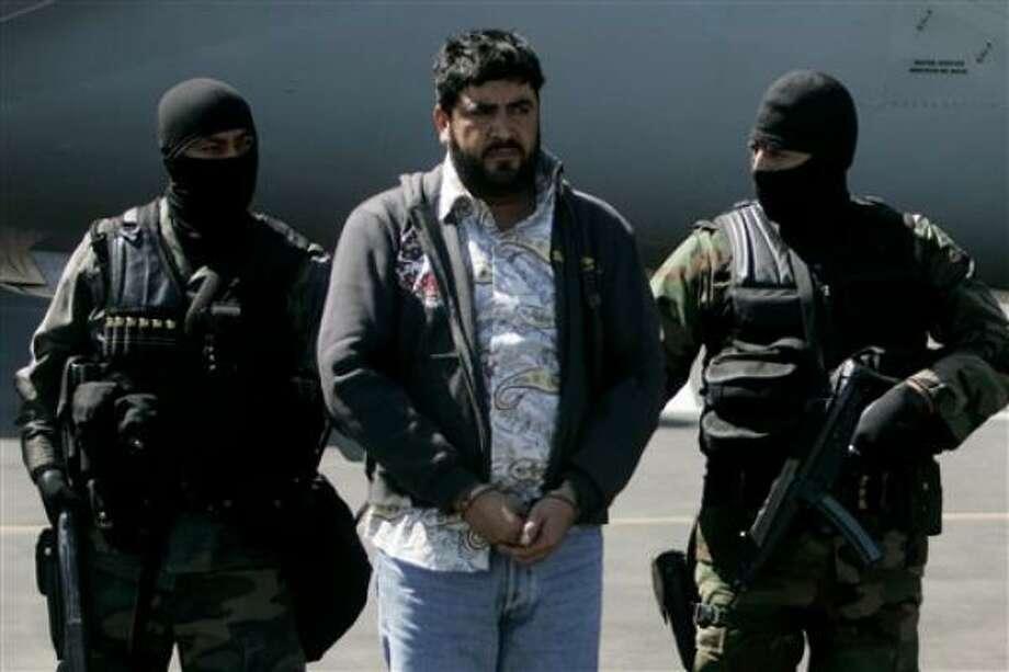 Mexican federal police officers escort Alfredo Beltran Leyva, known as El Mochomo, Monday at Mexico City's airport. Photo: Eduardo Verdugo, AP