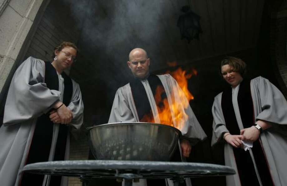 Youth director Mandy Jones, left, the Rev. Mark Welshimer and missions director Diane O'Brien of Houston's First United Methodist Church burn palms for ashes on Monday. Photo: SHARÓN STEINMANN, CHRONICLE
