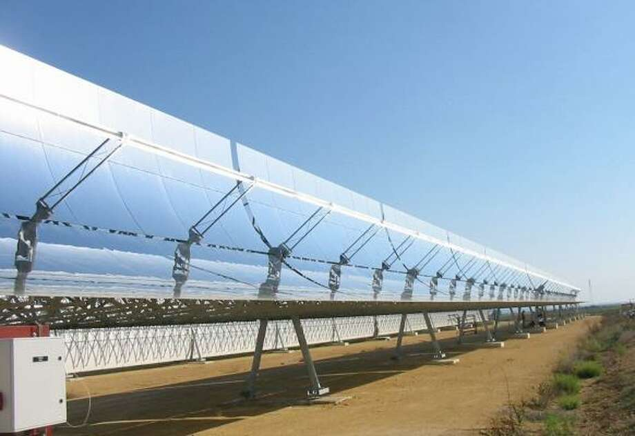 Long rows of mirrors track the sun from east to west, heating fluid in receiver pipes like a huge magnifying glass at an Abengoa plant outside Seville, Spain. Photo: ABENGOA SOLAR
