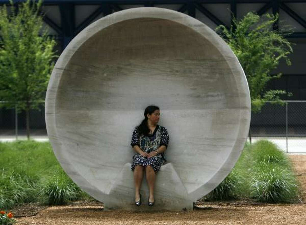 Vanessa Perez sits in one of Discovery Green's listening vessels on Thursday. The park is scheduled to open next Sunday.