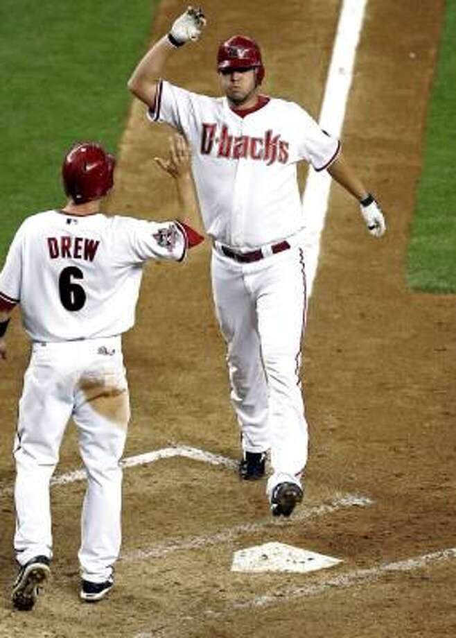 Arizona Diamondbacks pitcher Micah Owings high-fives teammate Stephen Drew after hitting a pinch-hit two-run home run against the Houston Astros during the sixth inning. Photo: Matt York, AP