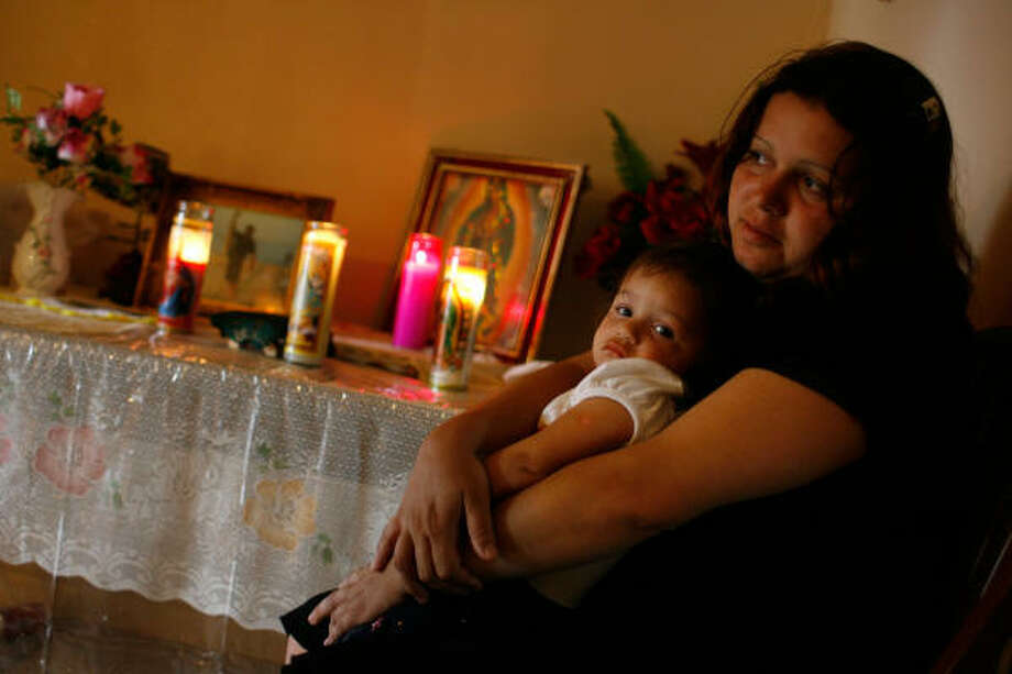 """Elena Garza holds daughter Natalie Selena Garcia, 1, beside an altar dedicated to her husband, Francisco Garcia, on Tuesday in her Houston home. """"I have never been in so much pain,"""" she says. """"I just have to remember all the happy memories he gave me."""" Photo: Sharon Steinmann, Chronicle"""