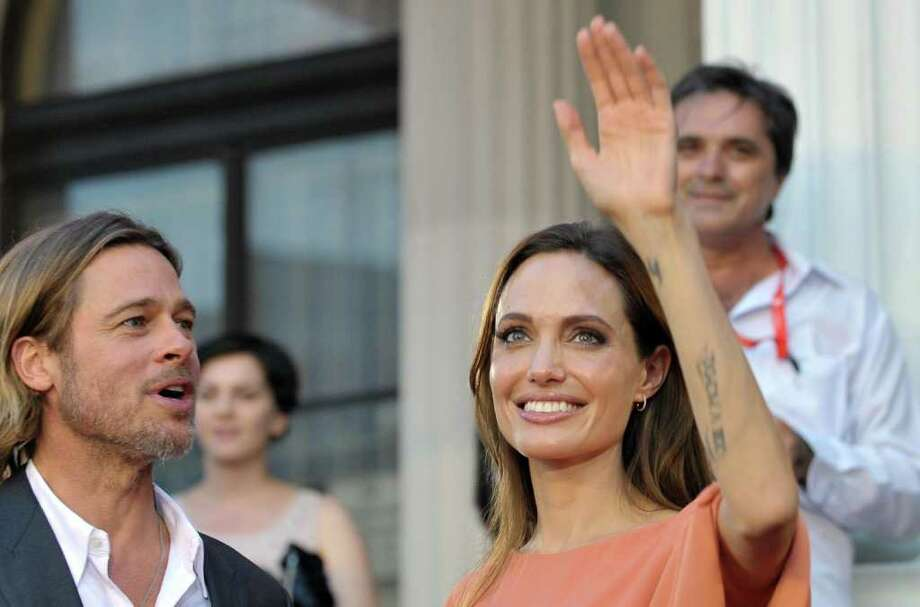 Angelina Jolie and Bred Pitt arrive on the red carpet during the final night of the 17th Sarajevo film festival in Sarajevo in Sarajevo, Bosnia, on Saturday, July 30,2011.  Angelina Jolie and Brad Pitt have arrived in Bosnia's capital to take part in the closing ceremony of the eight-day Sarajevo Film Festival. Festival organizers said Saturday the actress will be receiving a special award during the surprise visit. Jolie  visited Bosnia last year several times as UNHCR ambassador and drew attention to the plight of 117,000 people who haven't able to return to their homes even though the Bosnia war ended 15 years ago.(AP Photo/STR) Photo: Amel Emric / AP