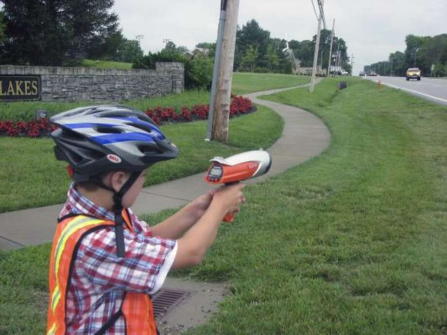Landon Wilburn, 11, points his Hot Wheels brand radar gun to see how fast an oncoming SUV is going in his Louisville, Ky., subdivision. Photo: Charlie White, AP