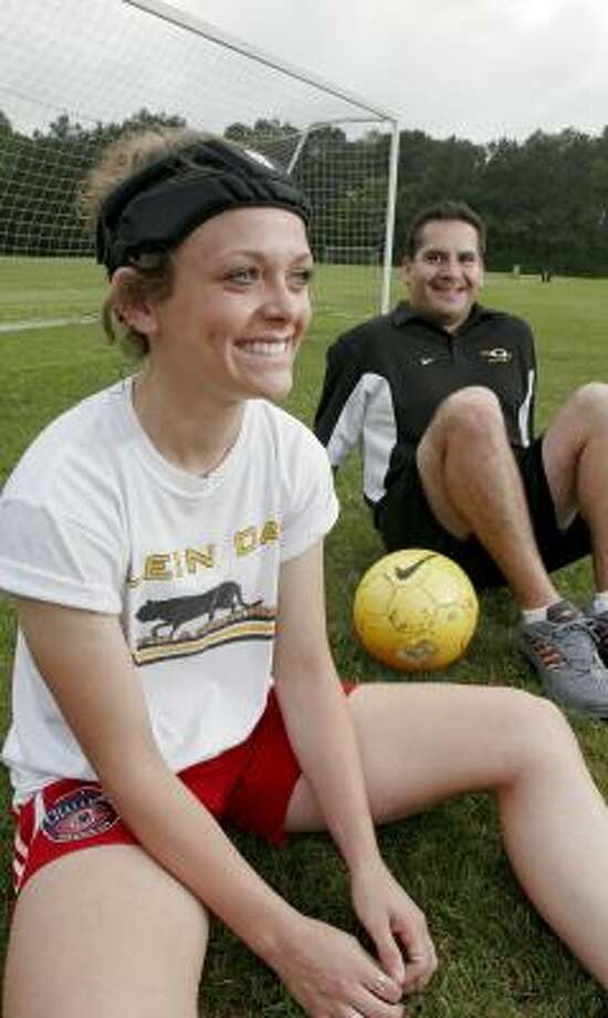 Melissa Kasper, 15, sits with Richie Sanchez, a Klein Oak High School girls soccer coach. Melissa suffered a concussion from mis-heading the ball. Even though protective headgear would not have prevented that particular head injury, she wears it now because it makes her feel safer. Photo: Bill Olive, For The Chronicle