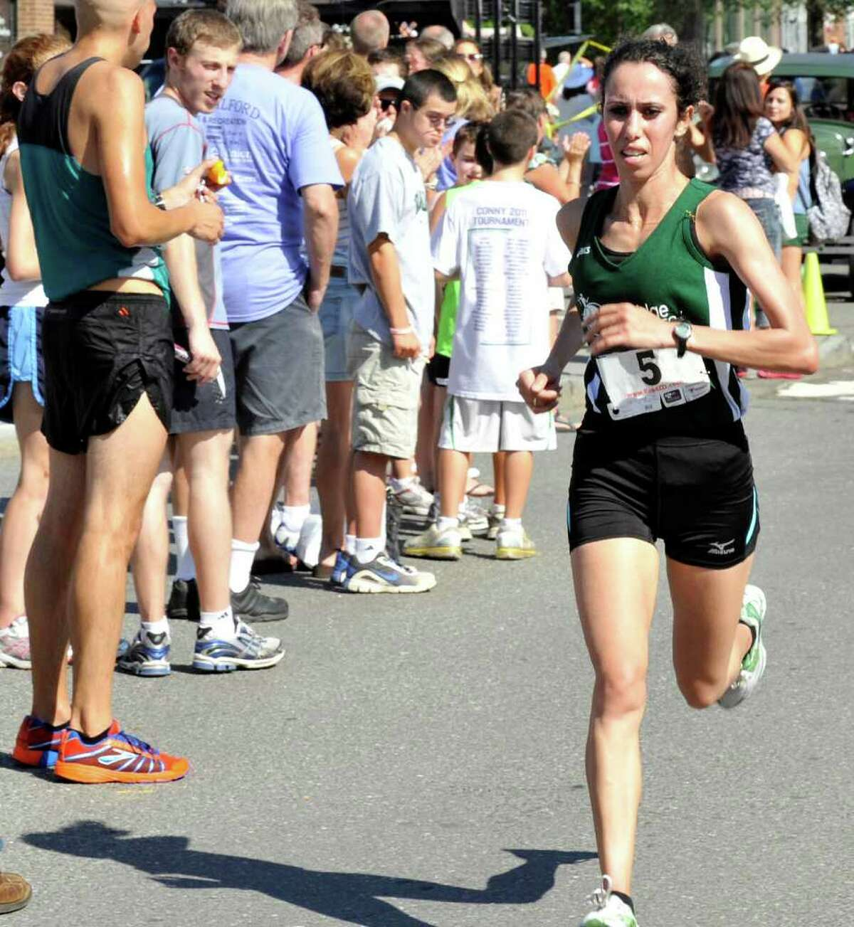 Malika Mejdoub, of New York City, wins the women's division of The New Milford 8-mile road race during Village Fair Days in New Milford, Saturday, July 30, 2011.