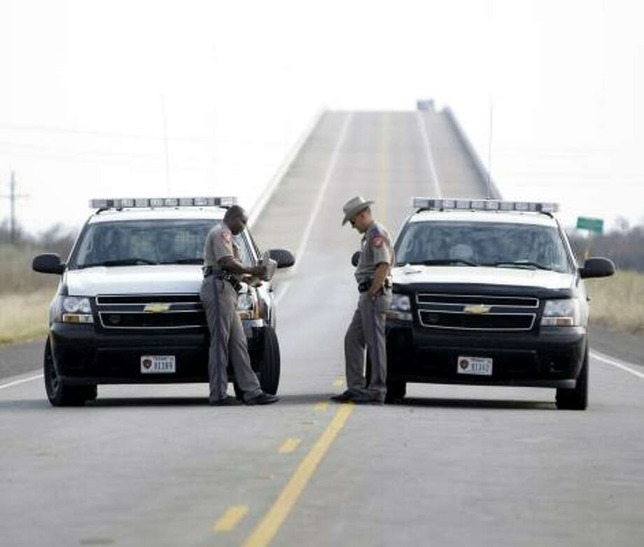 State troopers J. Jones, left, and R. Venegas, right, block entry into High Island on Highway 124 on Wednesday. Photo: KAREN WARREN, CHRONICLE