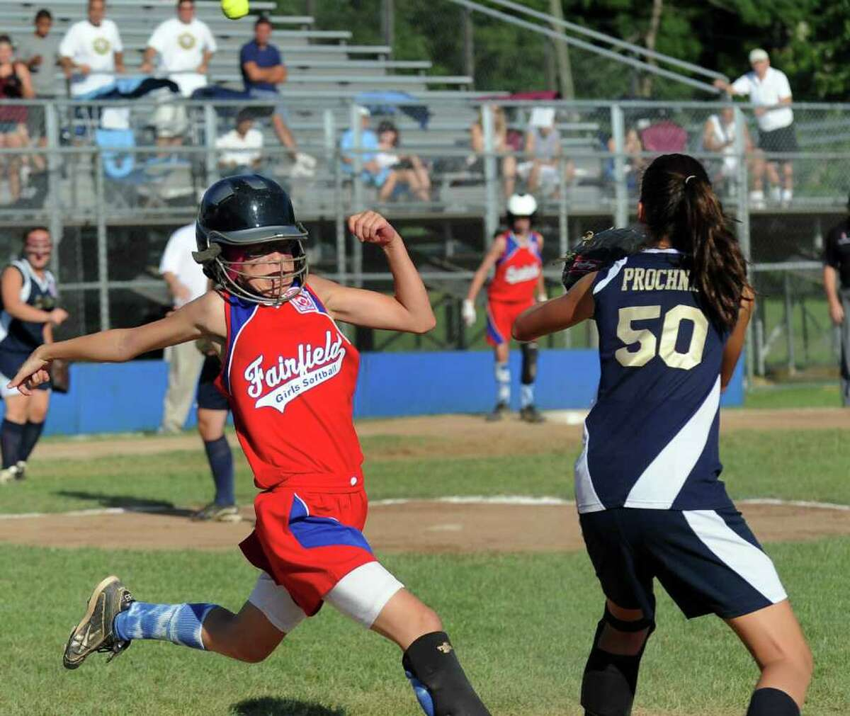 Fairfield's Mary Rose Finnegan beats the ball to first as New York's #50 Deana Prochnau waits, during Little League Softball Eastern Regional Championship game action in Bristol, Conn. on July 30, 2011. New York beat Fairfield 9-5.
