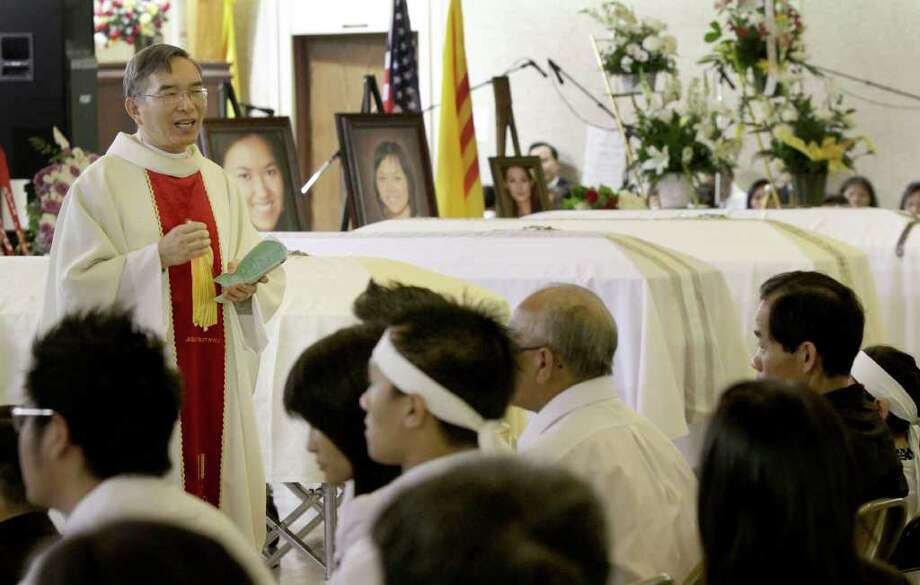 Rev. Peter Quang Le, left, of the Sacred Heart of Mary Church in Barling, Ark., on Saturday, July 30, 2011, conducts a service for four of the five victims of a shooting rampage last weekend at a Grand Prairie, Texas roller rink. Trini Do, 29, her sisters, Lynn Ta, 16, and Michelle Ta, 28, and her brother, Hien Ta, 21, were killed when her estranged husband opened fire during a birthday party for the couple's 11-year-old son. Tan Do, 35, later killed himself. Trini Do received a protective order in December against her husband, but she had it withdrawn earlier this year against a prosecutor's advice because she wanted to give him another chance, an aunt has said. (AP Photo/Danny Johnston) Photo: Danny Johnston, STF / AP
