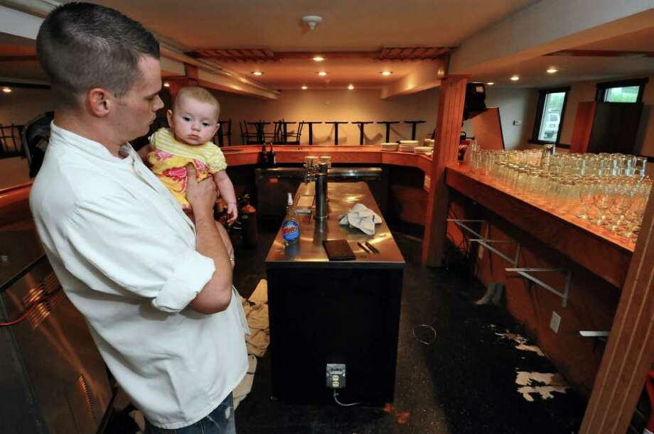 Horn's Tavern owner Brendan Horn holds his 4 month old daughter Makenna while taking a break from cleaning out his restaurant, which he and his wife Glenda had to close for financial reasons after 14 months of operation, on Tuesday July 26, 2011 in Brunswick, NY.   (Philip Kamrass / Times Union) Photo: Philip Kamrass / 00014029A