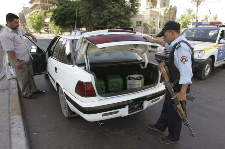 Police inspect a vehicle at a checkpoint in Baghdad. Iraq's government shut down the capital with a one-day curfew Saturday, ordering all cars and pedestrians off the streets and giving no reason for the measure. Photo: NAMIR NOOR-ELDEEN, REUTERS