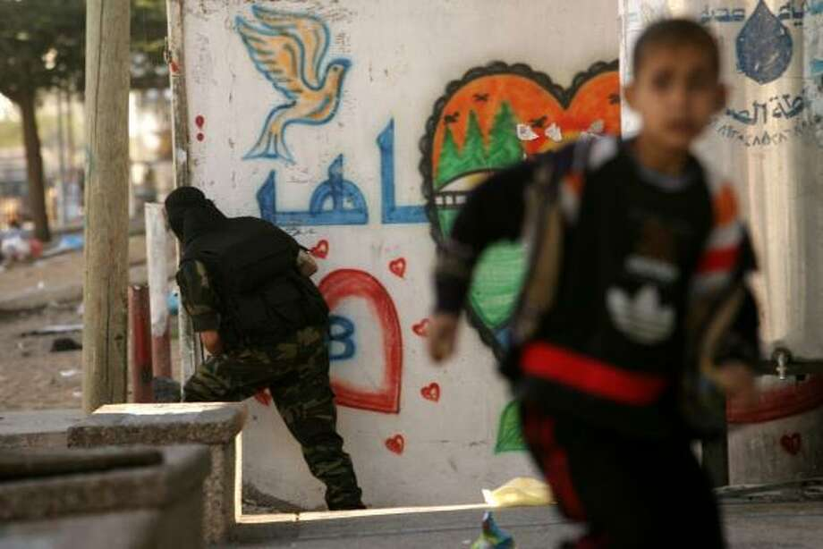 A Palestinian boy flees as a member of the Ezzedine al-Qassam Brigades, the armed wing of the ruling Hamas movement, takes up position Tuesday in Gaza City. Factional fighting between Hamas and Fatah forces continued despite Sunday's announced cease-fire. Photo: Abid Katib, Getty Images