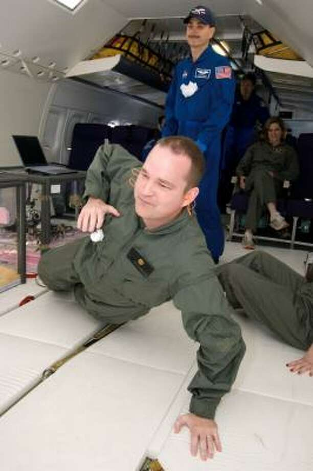 """Chron.com SciGuy Eric Berger performs a one-arm push-up as he flies aboard NASA's """"Weightless Wonder,"""" a military version of the DC-9 aircraft that flies parabolas in the atmosphere to produce zero-gravity conditions. NASA uses the flights to conduct experiments in micro-gravity. Photo: Photo Courtesy Of NASA"""