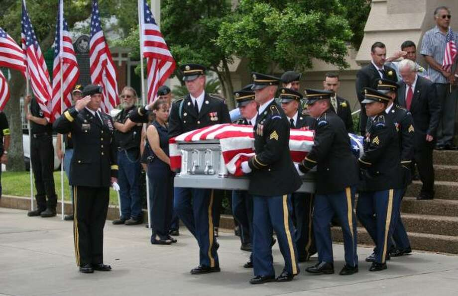 An honor guard from Fort Sam Houston removes the casket bearing the remains of Spc. Eddie Tamez on Saturday after services at a packed St. Patrick Catholic Church in Galveston. Photo: GARY FOUNTAIN, FOR THE CHRONICLE