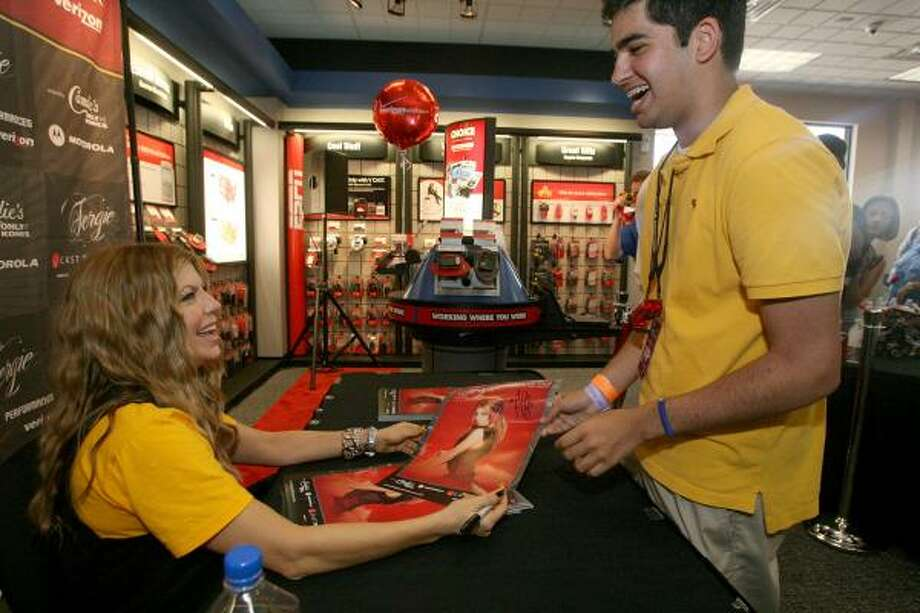 Fergie signs an autographs for Elah Nouri at Monday's grand opening of a Verizon Wireless store at the corner of Westheimer and Dunvale. Photo: Bill Olive, For The Chronicle
