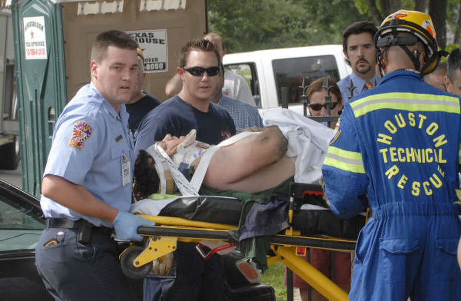 Houston Fire Dept rescue workers attend to a man who was trapped under a house at 941 Oxford today. Photo: TIM JOHNSON, For The Chronicle