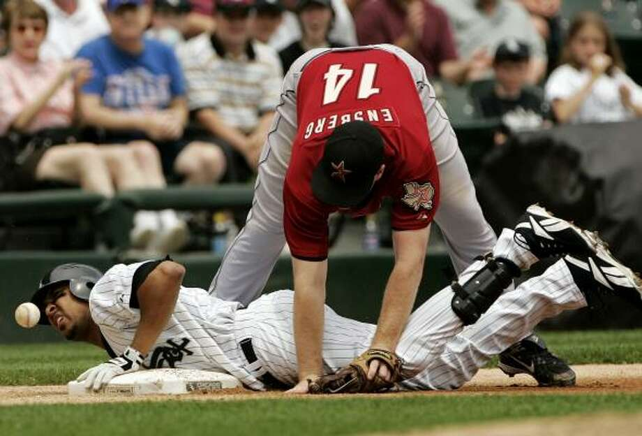 Luis Terrero of the White Sox slides under Morgan Ensberg to reach third base. Photo: JOSE M. OSORIO, MCCLATCHEY-TRIBUNE