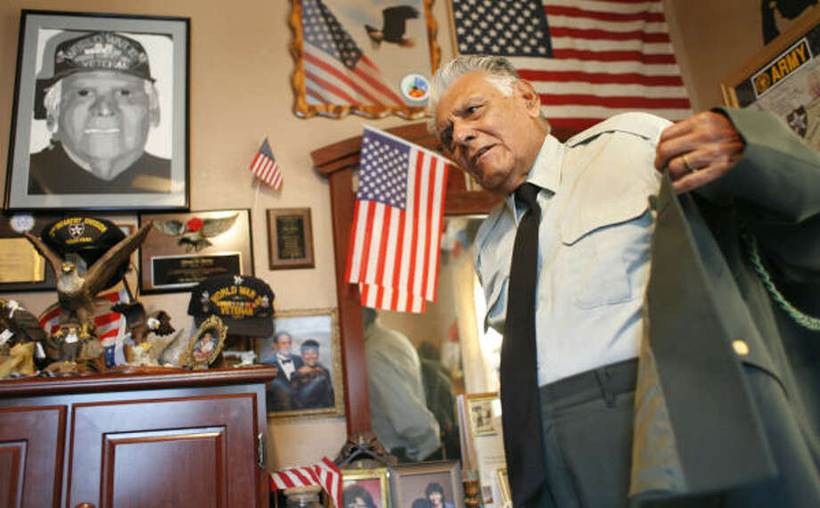 Johnnie Marino, 88, dons his uniform as he  shares his memories of the U.S. Army's 2nd Infantry Division. Among his World War II memorabilia, displayed in his home, are numerous medals and a portrait drawn of him by a child after he had spoken at a school. Photo: Steve Ueckert, Chronicle