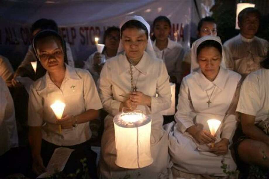 Catholic nuns and others gather outside the Myanmar embassy in Bangkok, Thailand on  Saturday to attend a candlelight vigil for those killed and injured in the recent crackdown in Myanmar. Photo: David Longstreath, AP