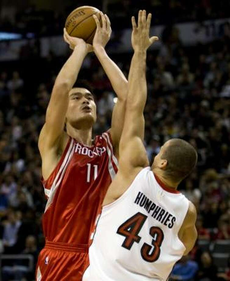 Yao Ming takes a shot over Toronto's Kris Humphries. Photo: Adrian Wyld, AP