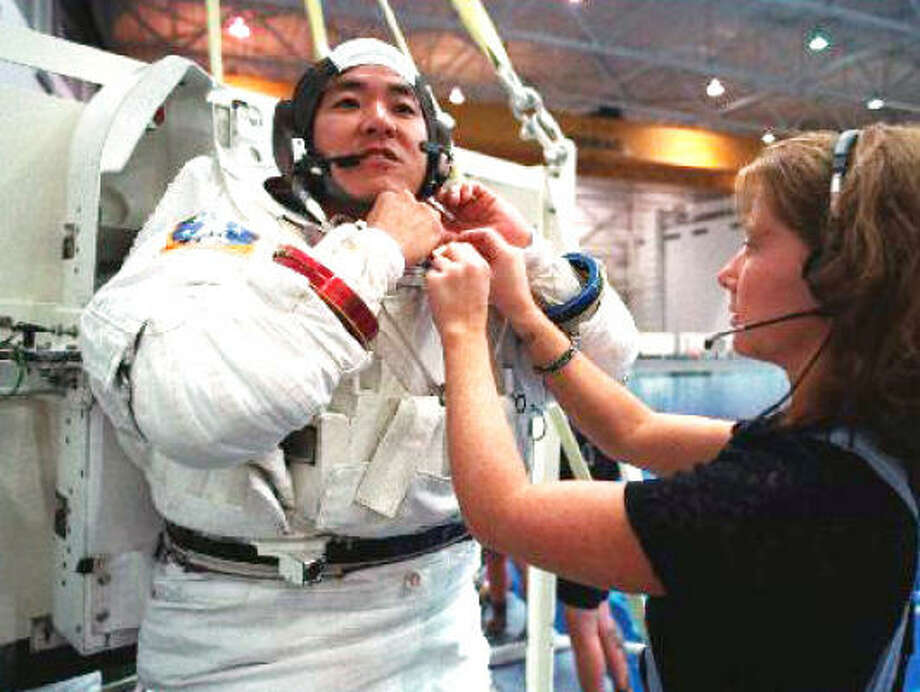 Astronaut Dan Tani gets help with his suit before a six-hour underwater training session at a NASA swimming pool in 2000. Photo: Steve Ueckert, Chronicle File