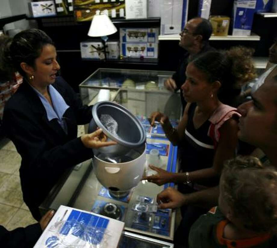 A vendor shows shoppers an electric rice cooker at a store in Havana. Cubans who can afford it are snapping up appliances and electronic goods now made available to the public by Raul Castro's government. Such goods previously were only for sale to foreigners. Photo: JAVIER GALEANO, ASSOCIATED PRESS