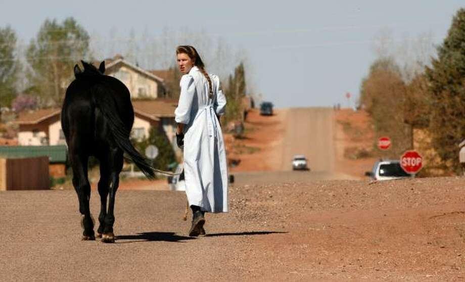A woman wearing traditional FLDS clothing walks her horse Monday. Female members of the church wear clothes wrist to ankle and keep their hair long. Photo: Johnny Hanson, Chronicle