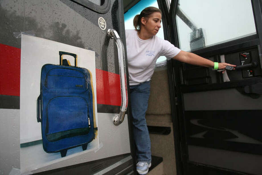 A photo of a piece of luggage shows what Halea Kersten, Texas EquuSearch volunteer, is looking for as the search continues for Randy Sylvester, 7, and Denim Sylvester, 3, on Thursday in Pasadena. Photo: Mayra Beltran, Chronicle