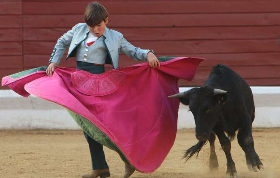 Ten-year-old Franco-Mexican bullfighter Michelito Lagravere fights a young bull in southwestern France earlier this week. Photo: BOB EDME, ASSOCIATED PRESS