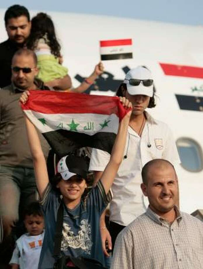 Repatriated Iraqis get off Iraqi Prime Minister Nouri al-Maliki's official airplane Sunday upon arrival from Egypt at Baghdad's airport. More than 200 Iraqis who had fled for safety returned. Photo: AHMAD AL-RUBAYE, AFP/GETTY IMAGES