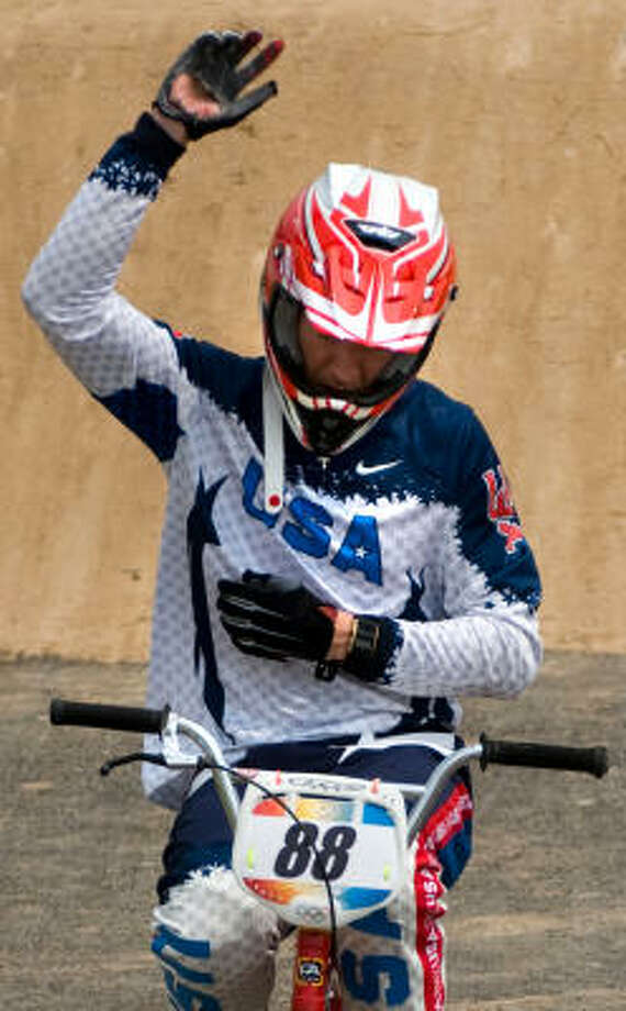 Kyle Bennett waves as he crosses he finish line on his own power while clutching his left arm to his chest after a crash during the quarterfinals of BMX cycling at the 2008 Summer Olympic Games on Wednesday in Beijing. Photo: Smiley N. Pool, Chronicle Olympics Bureau