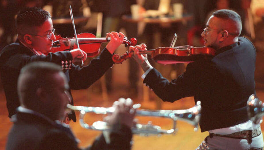 """Adrian Longoria, left, and Gabriel Cantu play dueling violins during their performance with """"Mariachi Imperial"""" on March 9, 2003. Photo: John Everett, Houston Chronicle"""