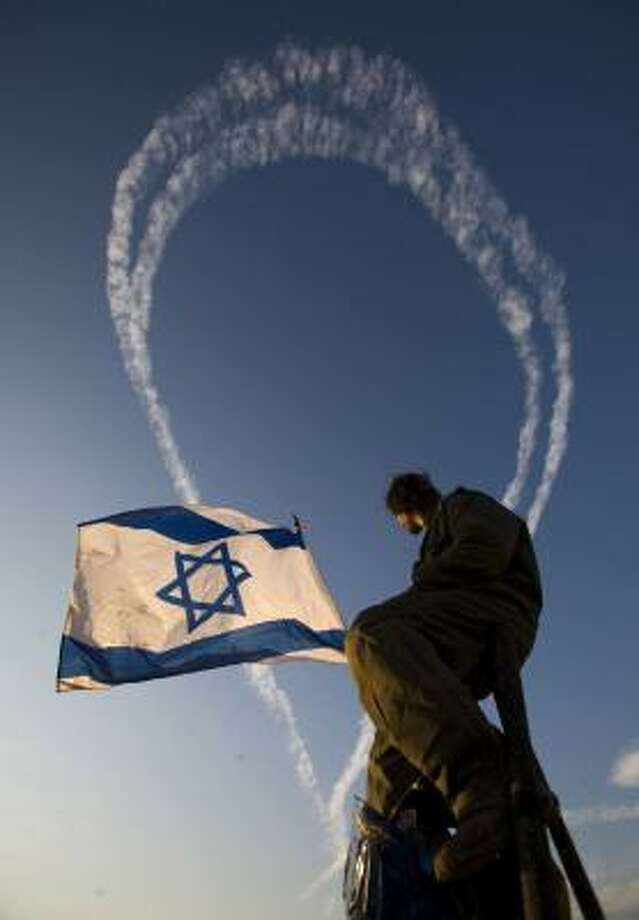 An Israeli watches from his side of the border as fighter jets fly over the northern Gaza Strip on Saturday. Photo: BERNAT ARMANGUE, ASSOCIATED PRESS
