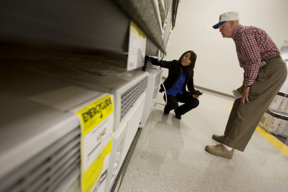 Larry Jackson shops for an air conditioner with sales associate Laura Pacheco at the Conn's on South Gessner. Photo: Sharon Steinmann, Chronicle