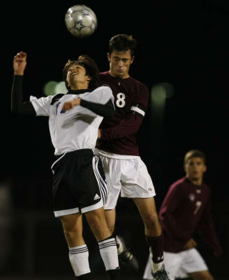 Cinco Ranch's Reagan Haisler, right, and Morton Ranch's Kevin Alvarenga go up for the ball in the second half in a District 17-5A soccer match at Morton Ranch on Tuesday in Katy. Photo: Julio Cortez, Chronicle