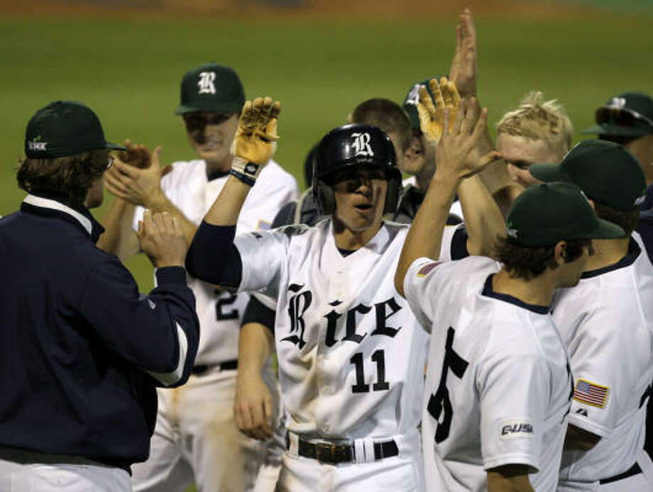 Rice's Rick Hague, center, receives congratulations after hitting a two-run home run in the fifth inning against Texas Tuesday night. Photo: Bob Levey, For The Chronicle