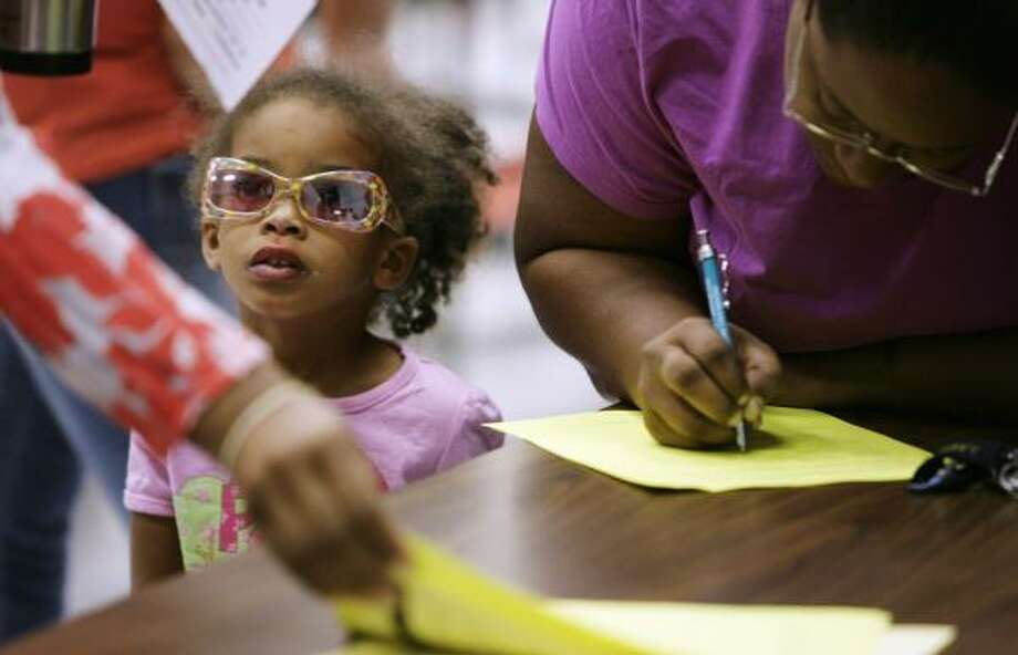 Nyjala Bush, 3, stands by as mother Adrienna Fields gets another daughter enrolled at Rosenberg Elementary. Photo: ERIC KAYNE, CHRONICLE