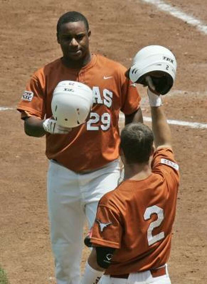 Texas' Kevin Keyes, left, in congratulated by teammate Travis Tucker, right, after scoring against Kansas State in the fifth inning of a Big 12 baseball tournament game in Oklahoma City, Saturday, May 23, 2009. Texas won the game 4-2. Photo: Associated Press