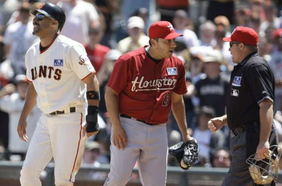 Russ Ortiz, center, argues a call to no avail as the Giants' Randy Winn scores on a wild pitch during the fifth inning. Photo: Ben Margot, AP