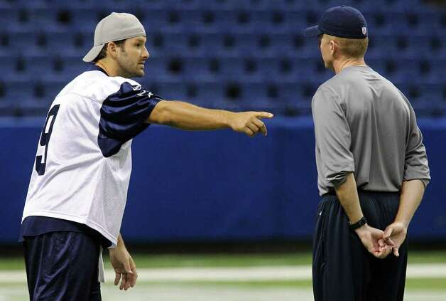 Quarterback Tony Romo (left) talks with head coach Jason Garrett during the morning session of the Dallas Cowboys training camp at the Alamodome on Saturday, July 30, 2011. Kin Man Hui/kmhui@express-news.net Photo: KIN MAN HUI, : / SAN ANTONIO EXPRESS-NEWS