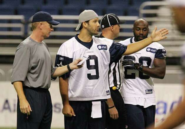 Quarterback Tony Romo goes over plays with head coach Jason Garrett during the morning session of the Dallas Cowboys training camp at the Alamodome on Saturday, July 30, 2011. Kin Man Hui/kmhui@express-news.net Photo: KIN MAN HUI, : / SAN ANTONIO EXPRESS-NEWS