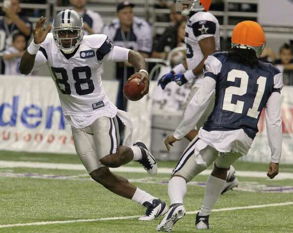 Wide receiver Dez Bryant (88) runs around cornerback Mike Jenkins (21) during the afternoon session of the Dallas Cowboys training camp at the Alamodome on Saturday, July 30, 2011. Kin Man Hui/kmhui@express-news.net Photo: KIN MAN HUI, : / SAN ANTONIO EXPRESS-NEWS