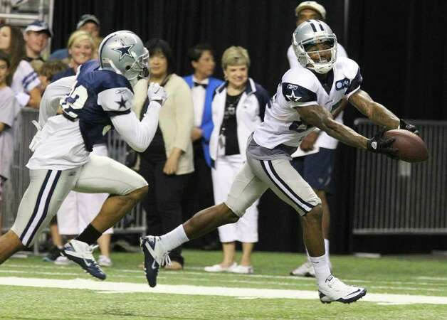 Wide receiver Kevin Ogletree (85) makes a finger-tip catch of a pass against Orlando Scandrick (32) during the afternoon session of the Dallas Cowboys training camp at the Alamodome on Saturday, July 30, 2011. Kin Man Hui/kmhui@express-news.net Photo: KIN MAN HUI, : / SAN ANTONIO EXPRESS-NEWS