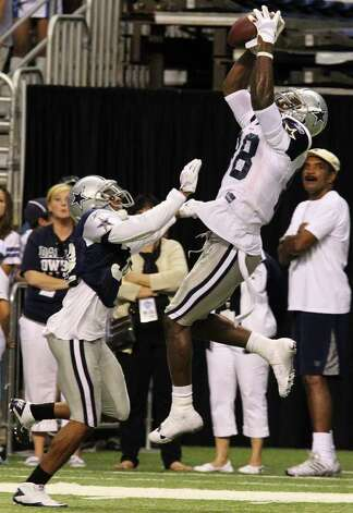 Wide receiver Dez Bryant (right) makes a high-flying catch over cornerback Orlando Scandrick (32) during the afternoon session of the Dallas Cowboys training camp at the Alamodome on Saturday, July 30, 2011. Kin Man Hui/kmhui@express-news.net Photo: KIN MAN HUI, : / SAN ANTONIO EXPRESS-NEWS